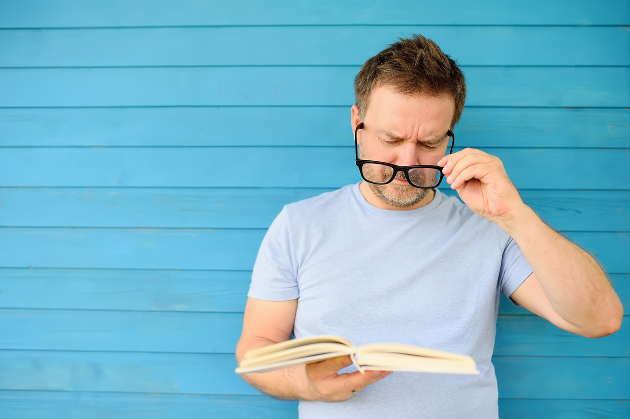 Portrait of mature man with big black eye glasses trying to read book but having difficulties seeing text because of vision problems