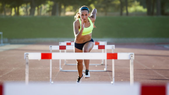Young athlete jumping over a hurdle during training on race track.