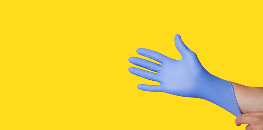 Hands wearing a blue latex glove, isolated on yellow background
