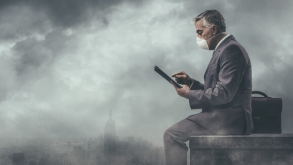 Businessman,Sitting,On,A,Rooftop,In,A,Polluted,City,And